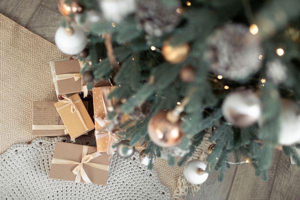 Closeup of Christmas gifts under snowly decorated fir tree with pastel brown ornaments.