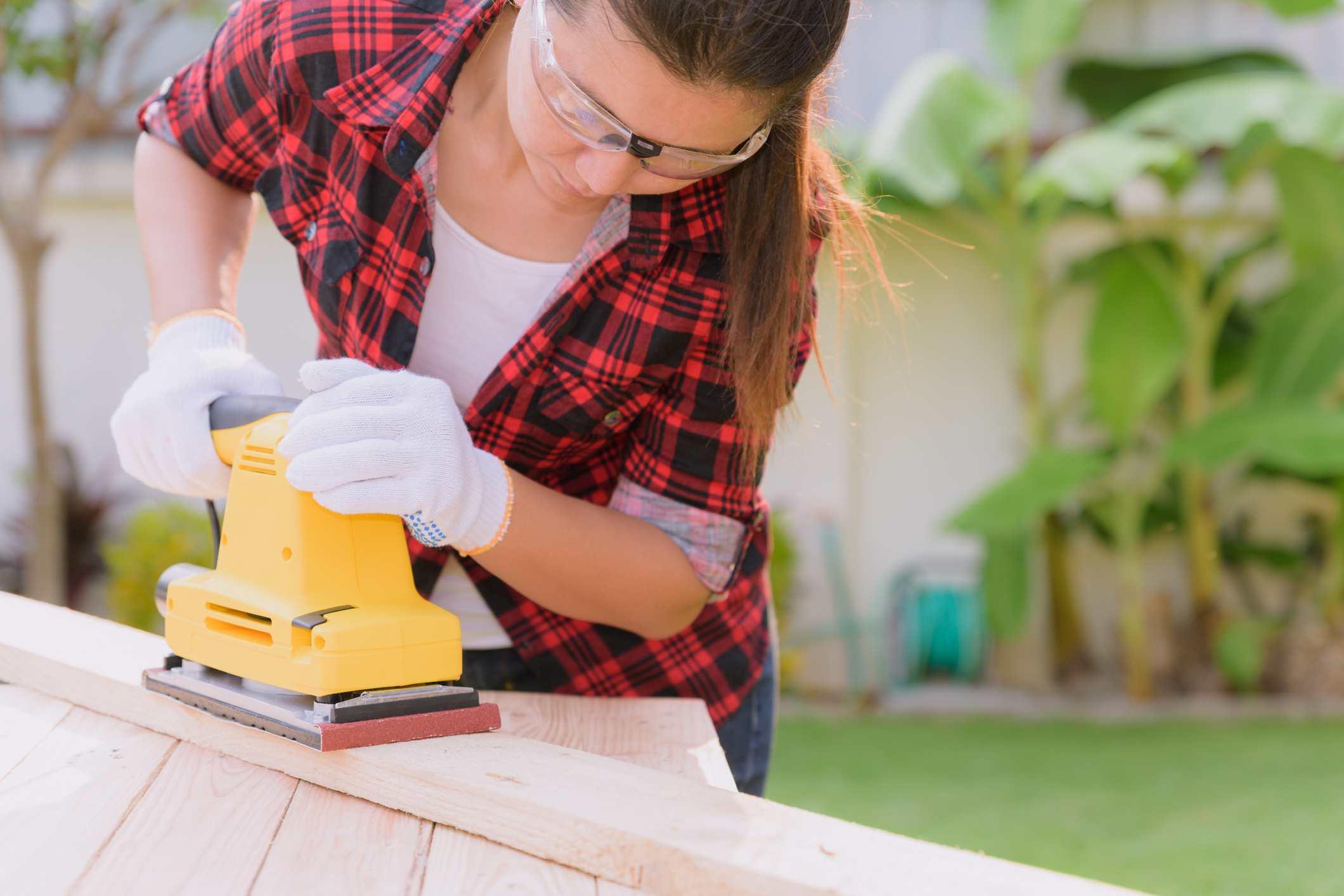 A woman hand sanding a piece of wood