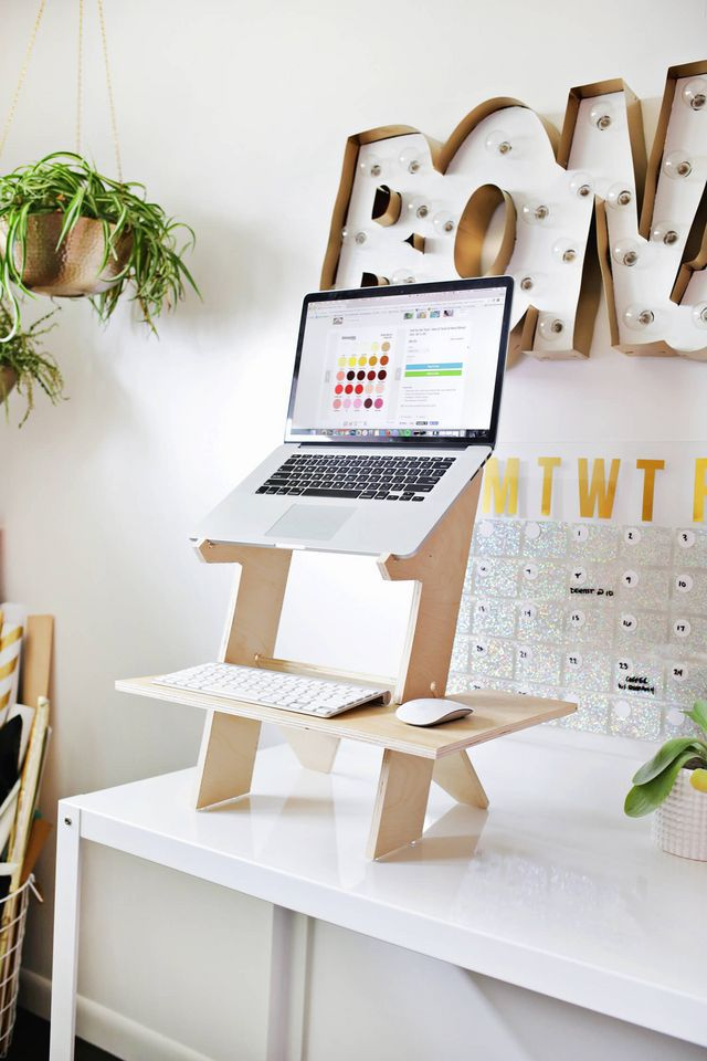 A tall tabletop wooden desk with a laptop on it.