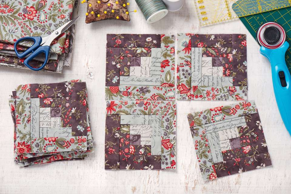Patchwork log cabin blocks, stack of blocks, sewing accessories on white wooden surface