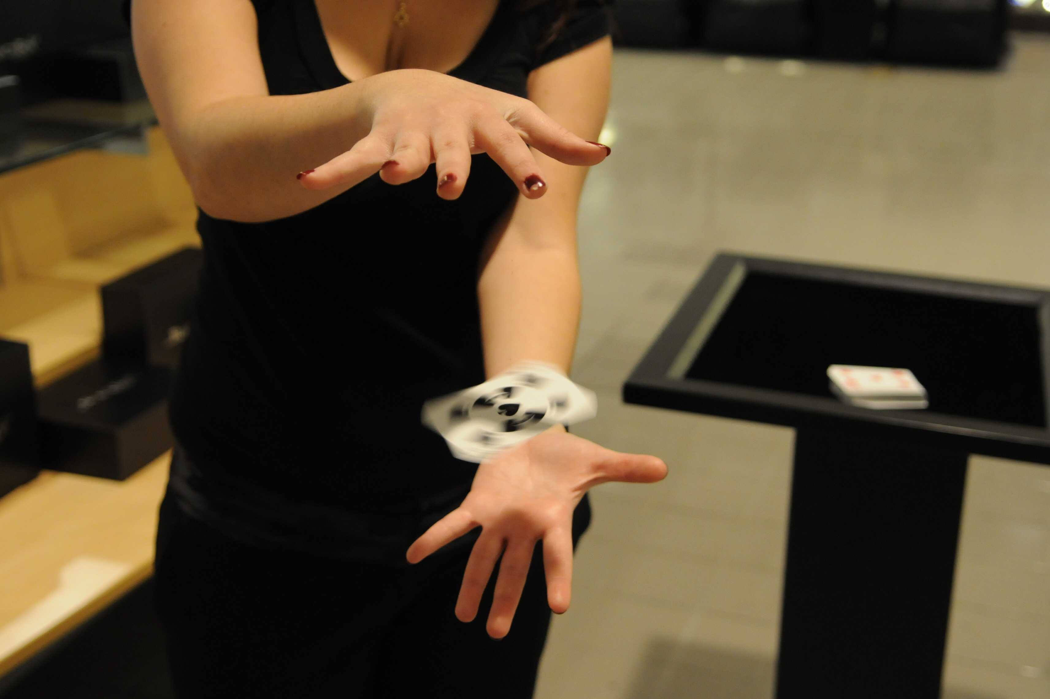 Woman performing magic to float and spin playing card