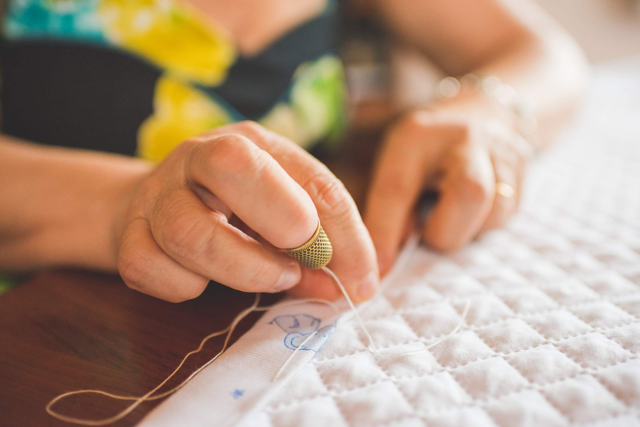 Cropped view of woman sewing hem on quilt