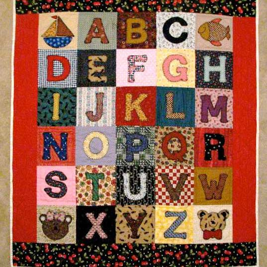 Red alphabet quilt with sailboat, fish, and animal heads.