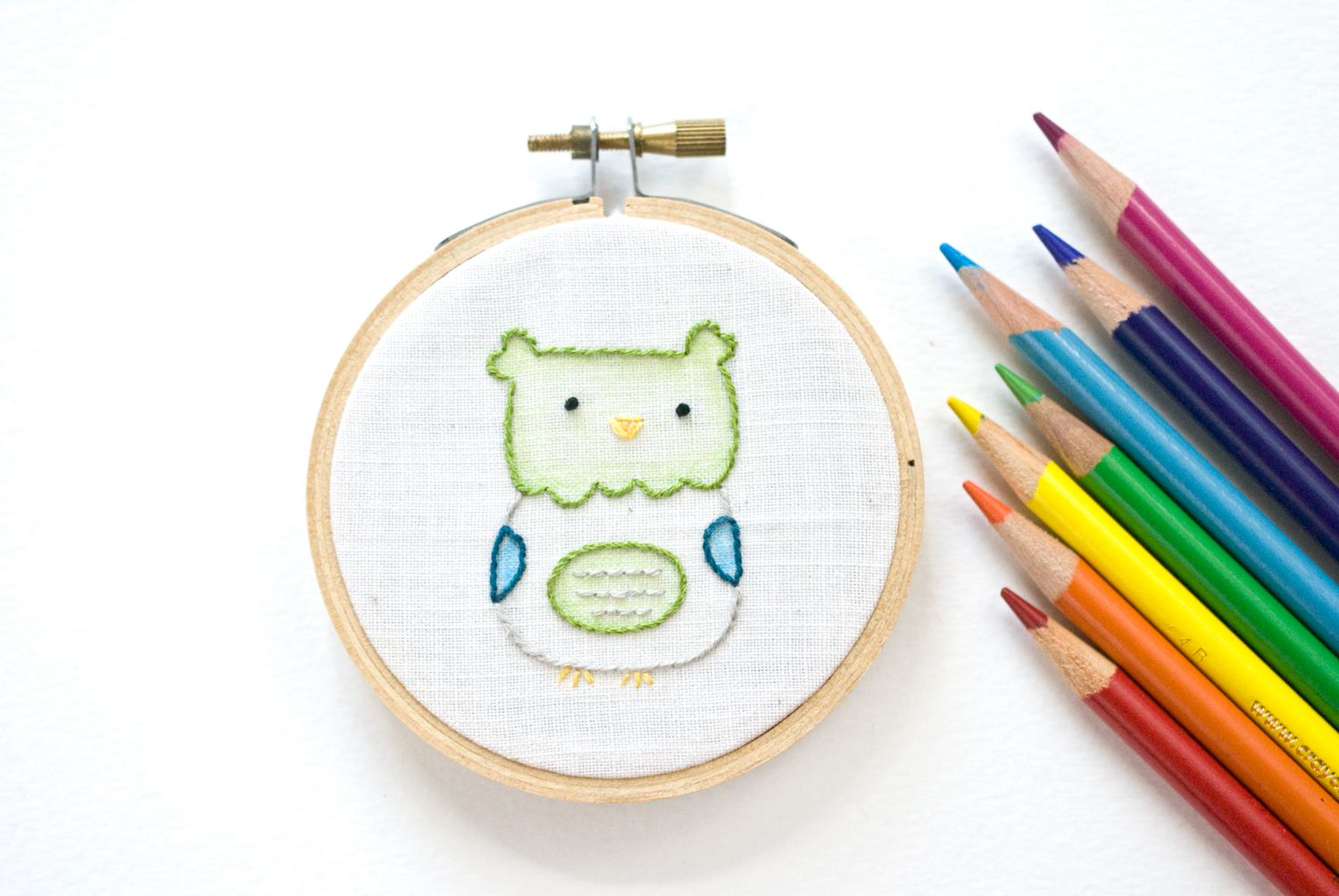 Completed embroidery in a hoop with colored pencils nearby.