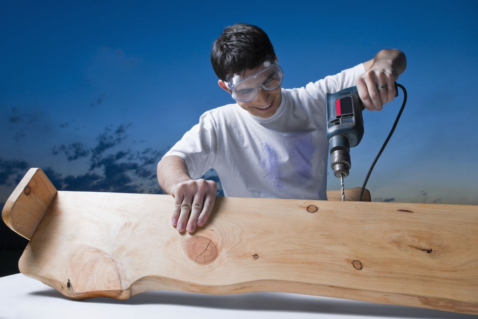 Mid adult man drilling in a wood plank