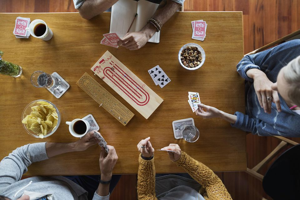 Overhead view of young friends playing cribbage table