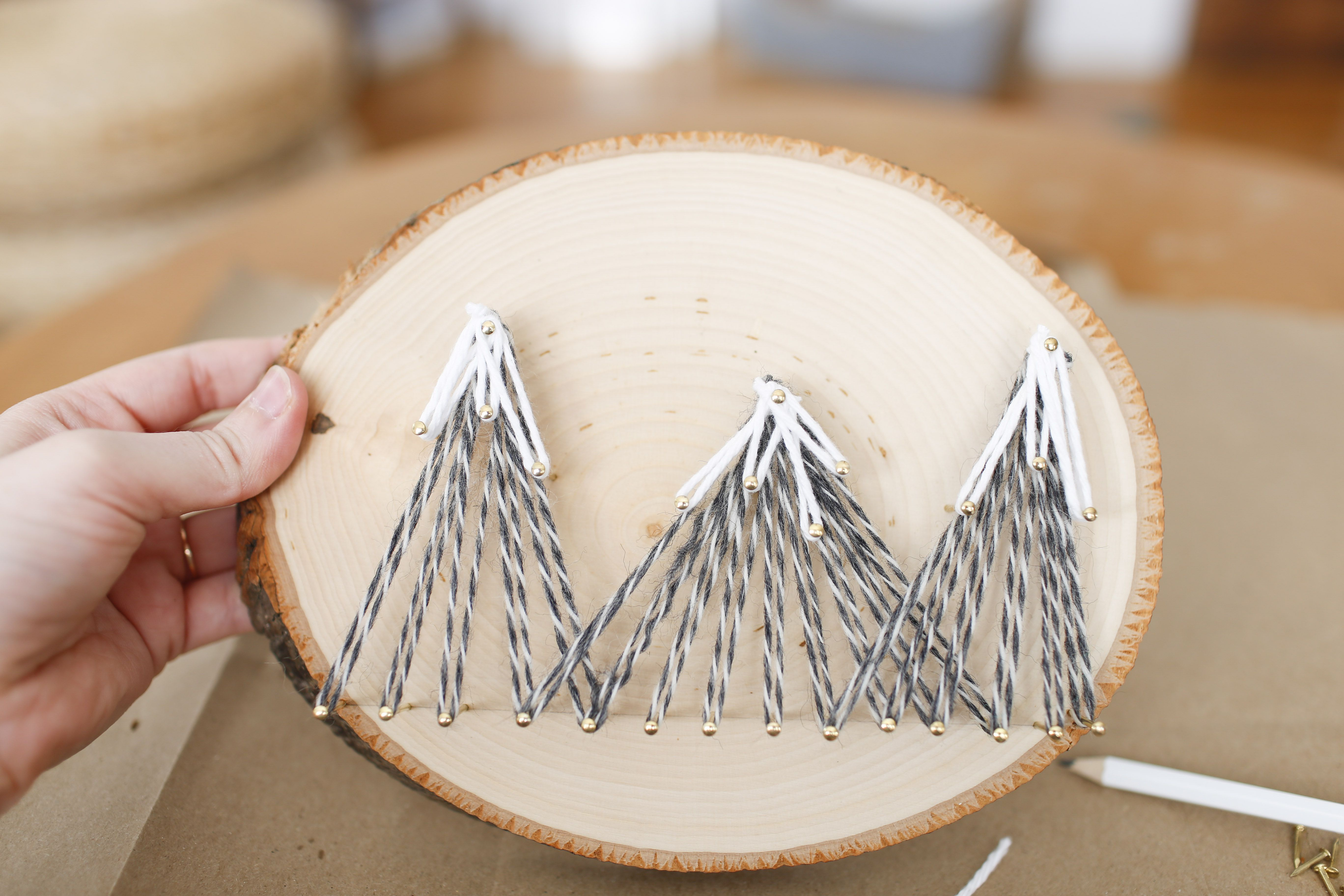 Hand holding mountain string art