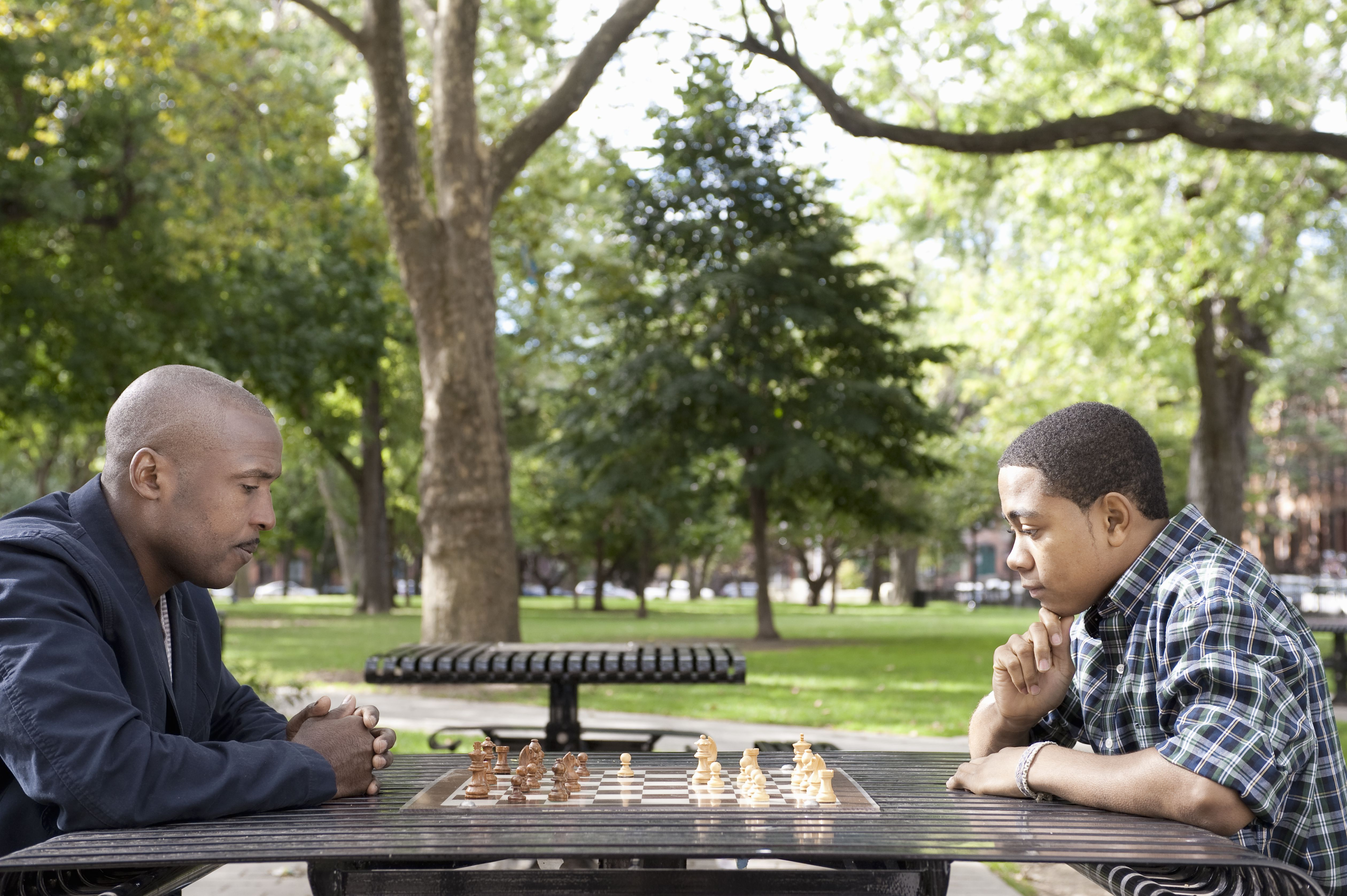 Teen Boy and Senior Man Playing Chess