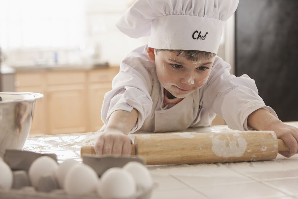 Young boy baking in chef's whites