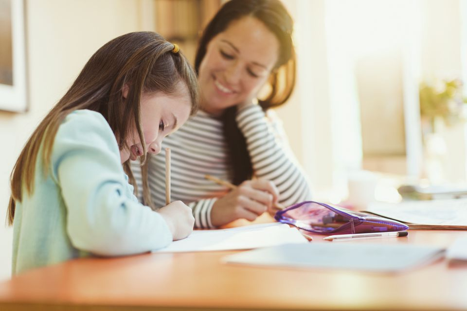 Mother watching daughter do homework