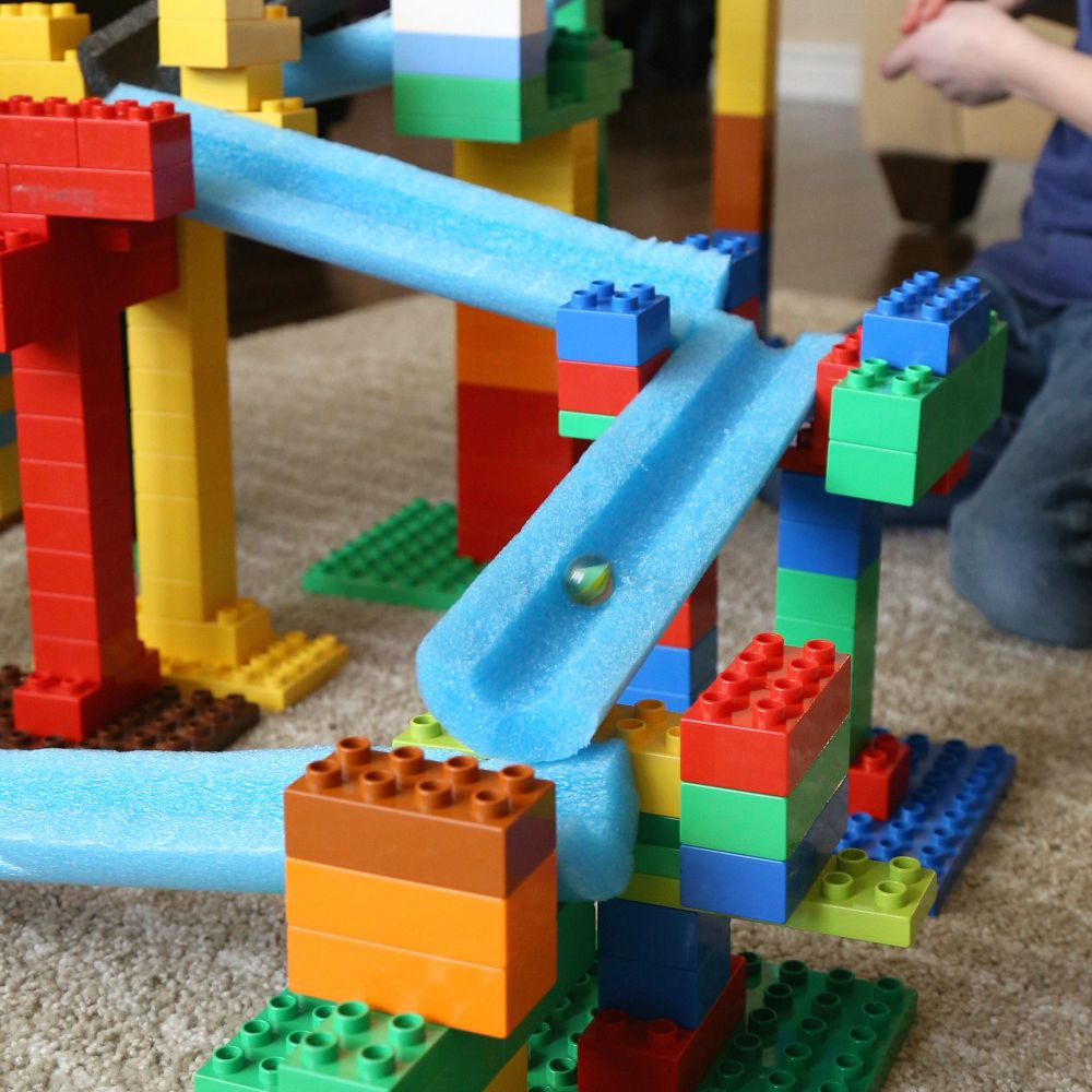Pool noodle marble run with Lego bricks.