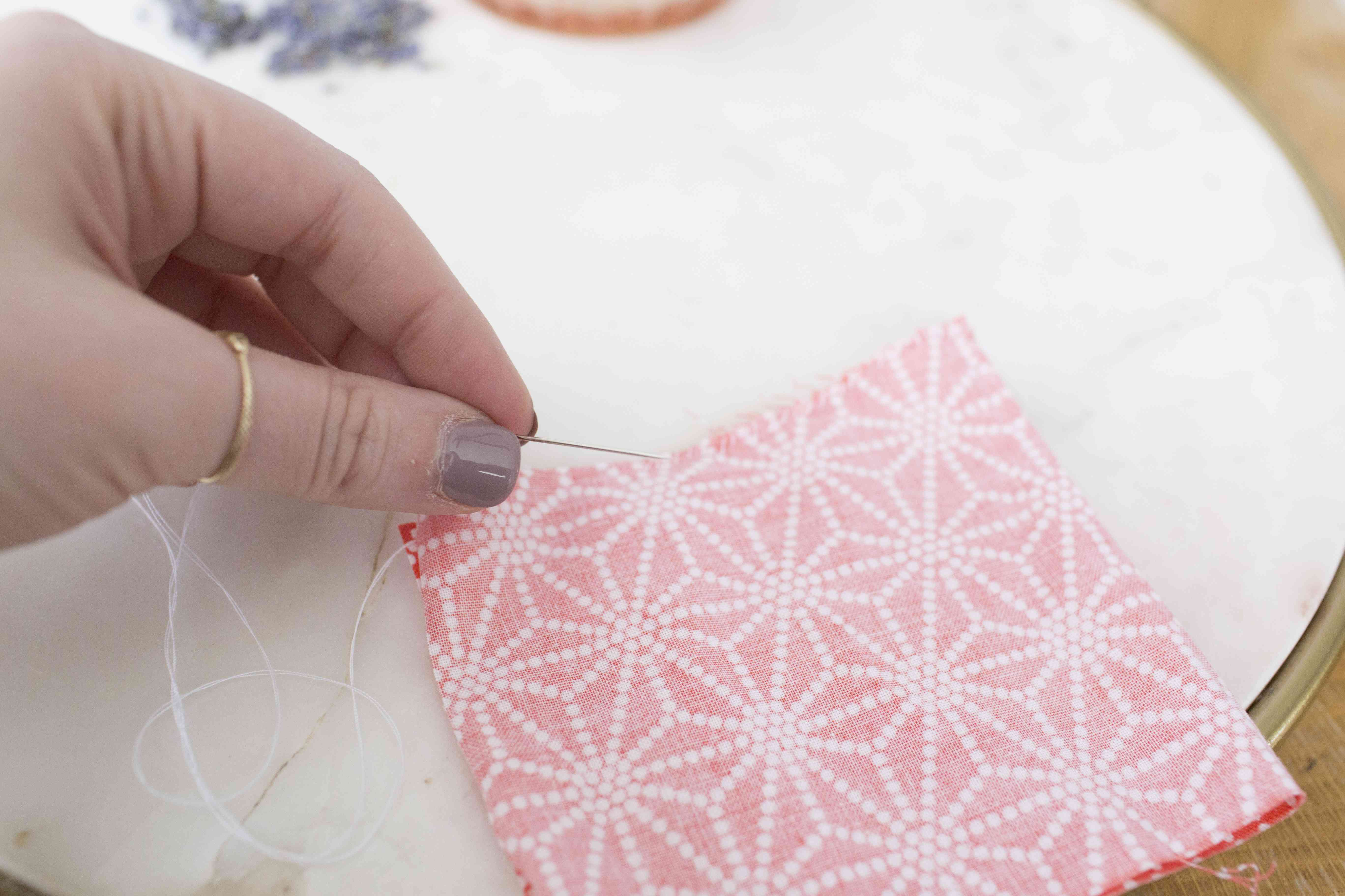 A woman's hand holding a needle fabric that is being sewn up