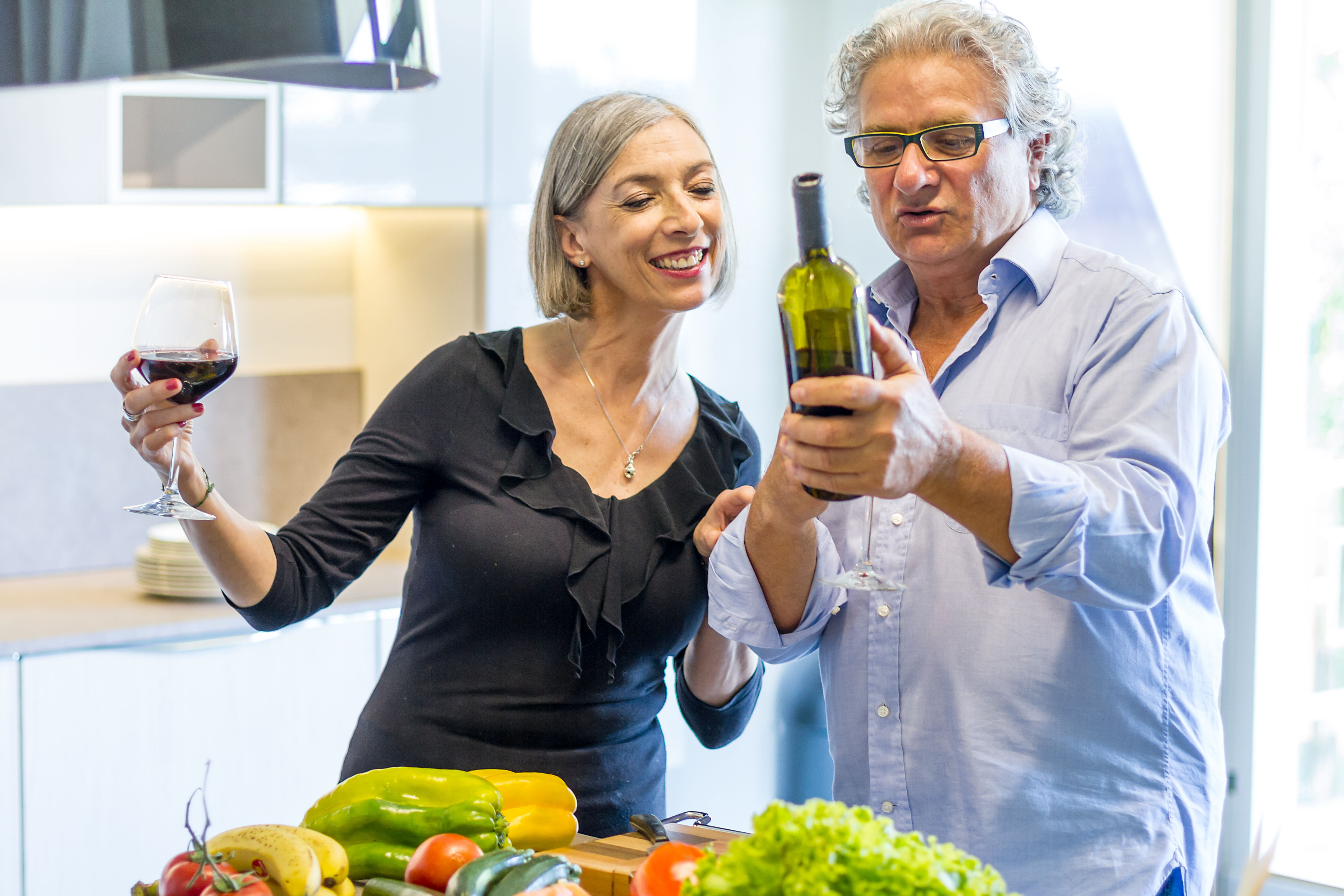 Couple of seniors tasting wine at home