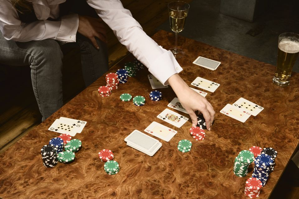 Young woman playing poker, gathering winnings, close-up