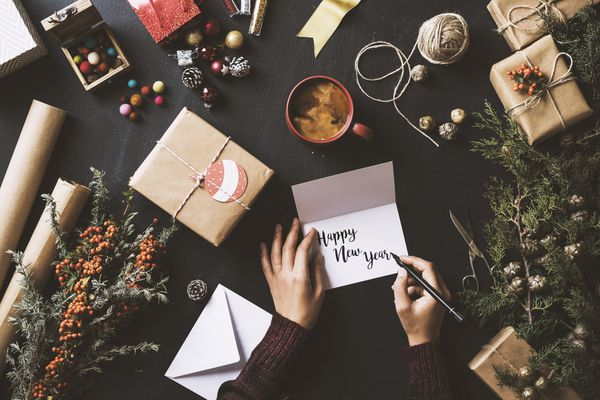 Person writing New Year cards surrounded by presents and decorations.