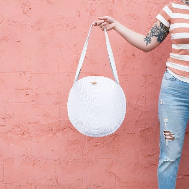 A woman holding a white circle tote