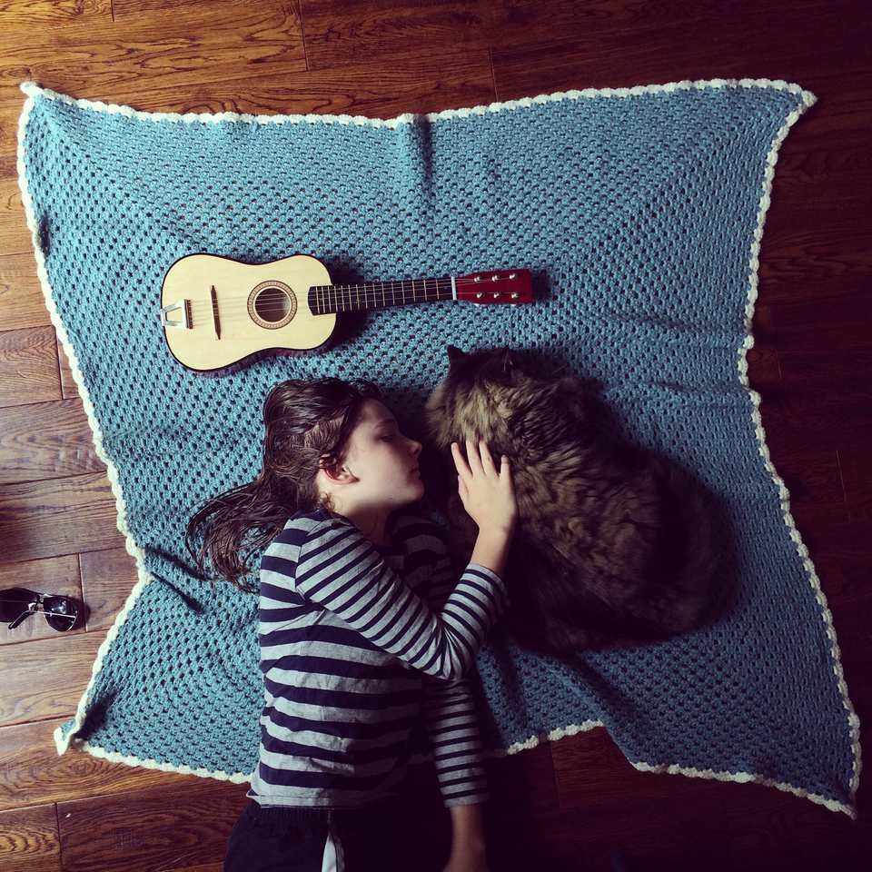 girl petting cat on top of crocheted blanket