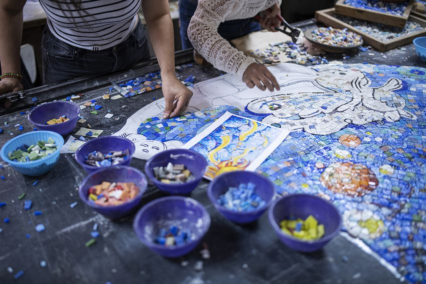 Two female artist working on mosaic project in workshop