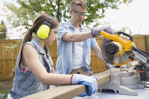Father and daughter using a miter saw