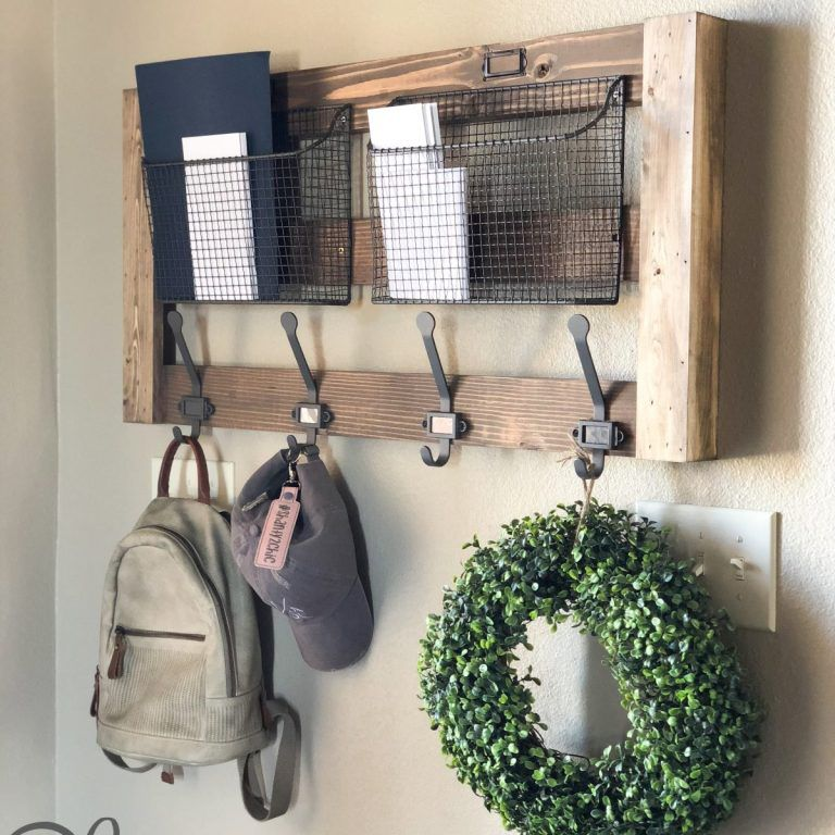 diy wall organizer with metal hooks. A backpack, hat, and wreath are hanging from it