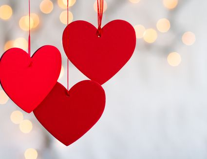 Three hanging red hearts on defocused light background