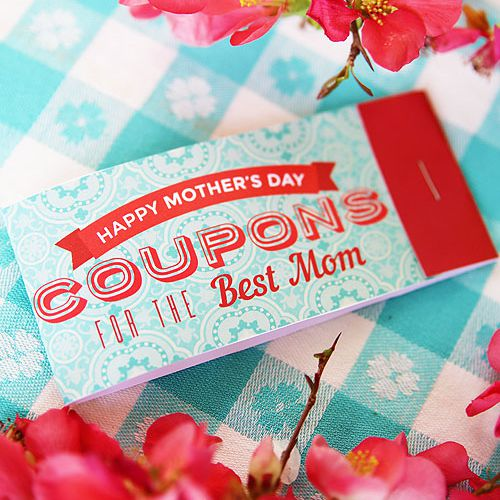 A photo of a Mother's Day coupon book on a table surrounded by pink flowers.