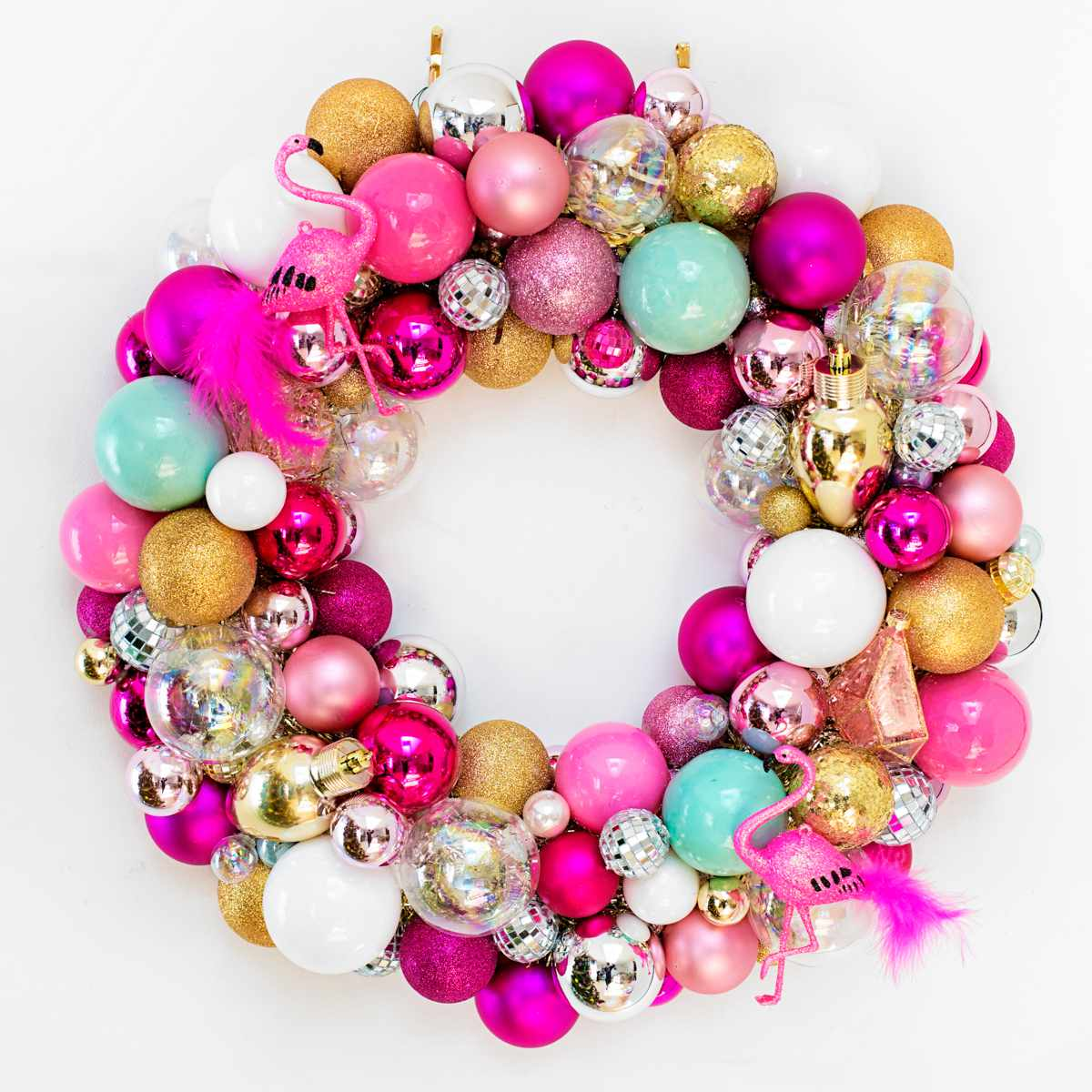 a wreath made of bright christmas balls and flamingo ornaments