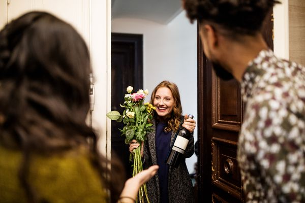 Woman holding bouquet and wine bottle while visiting friends