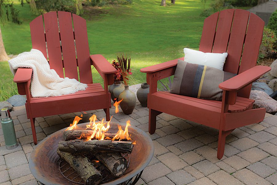 Two red Adirondack chairs by a fire pit.