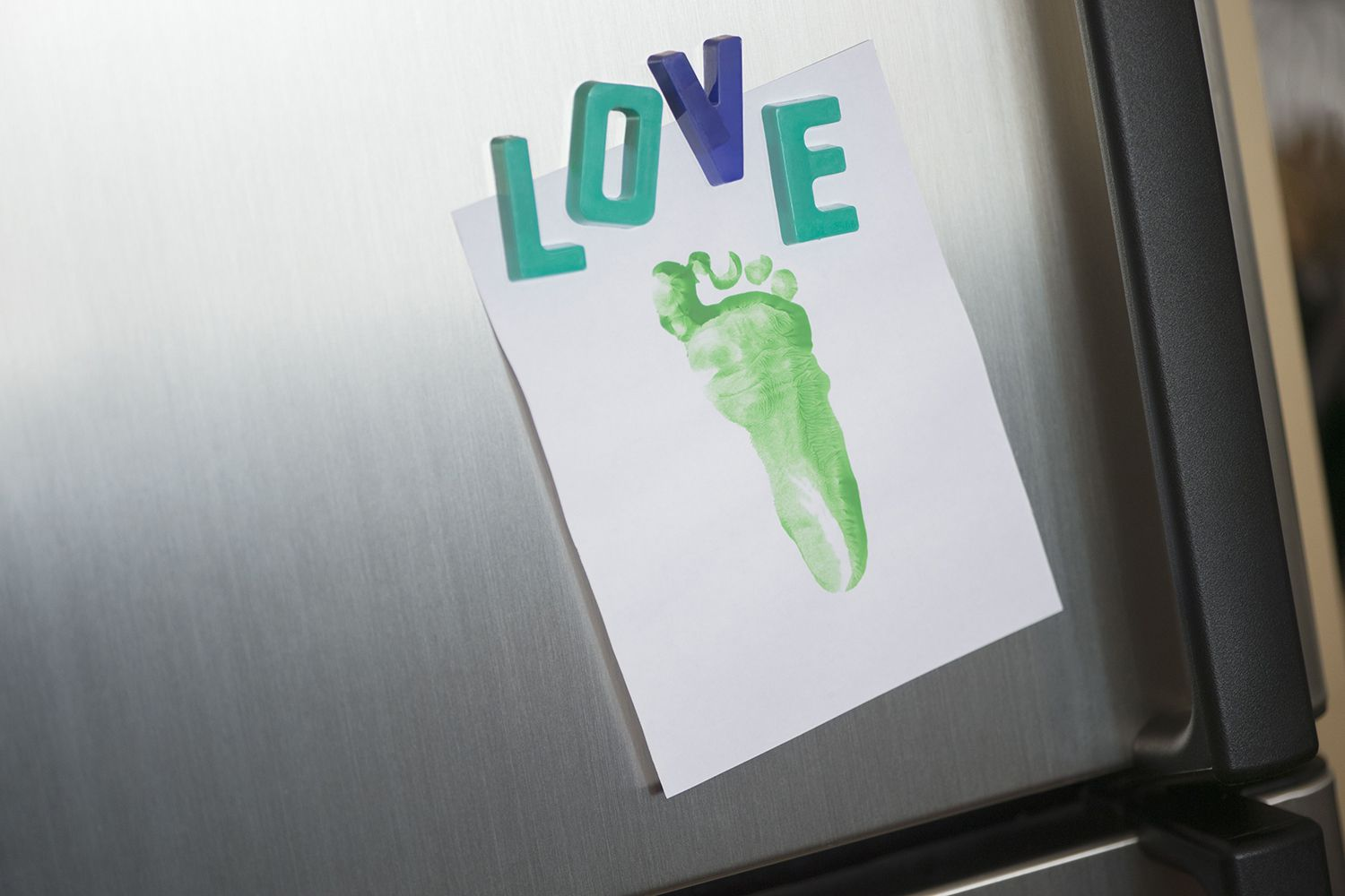 Close up of Love Magnets and Footprint on Refrigerator