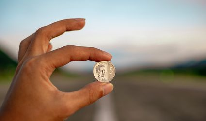 A person's hand holding up a coin with a blurred background