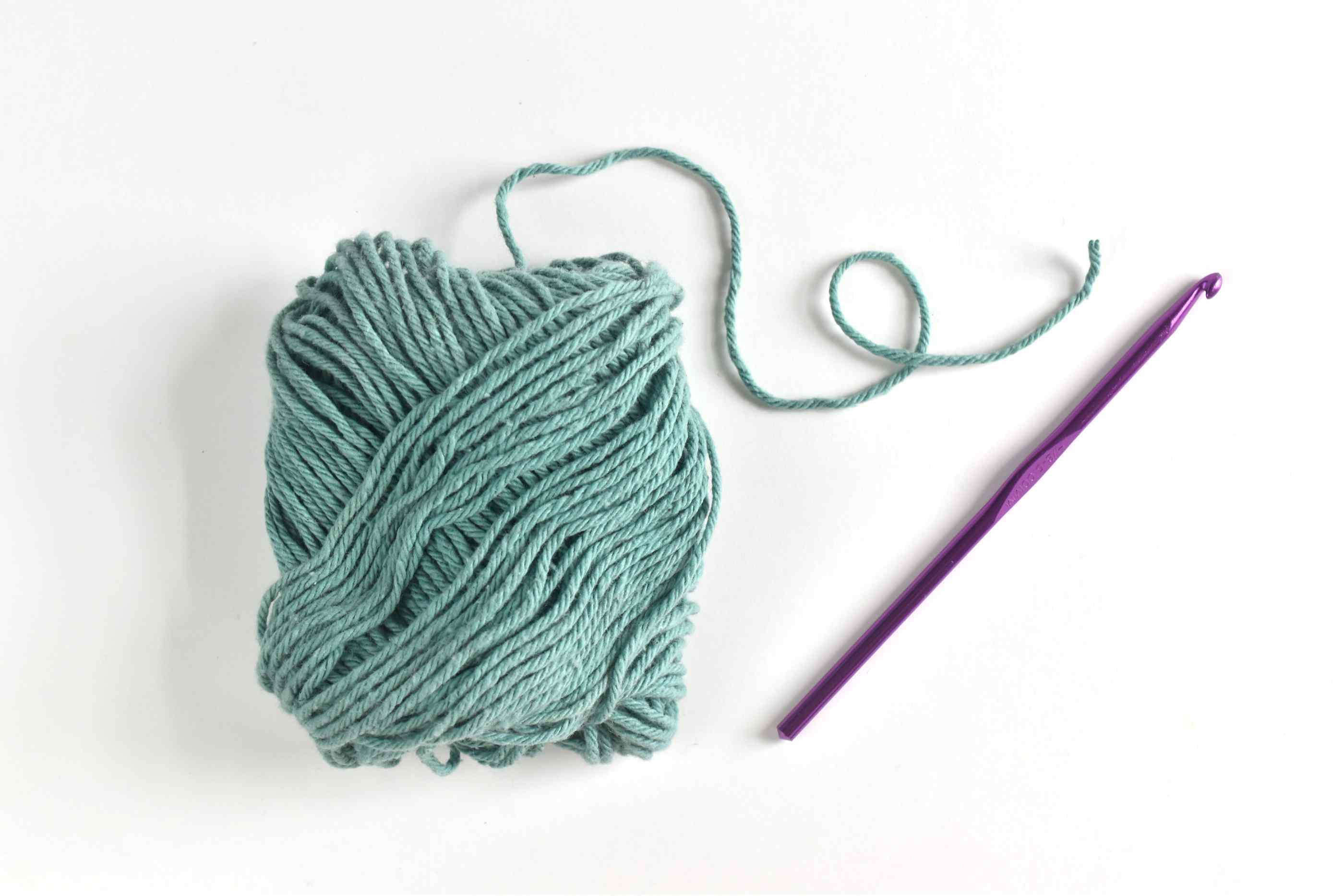 Ball of teal yarn and purple crochet hook.