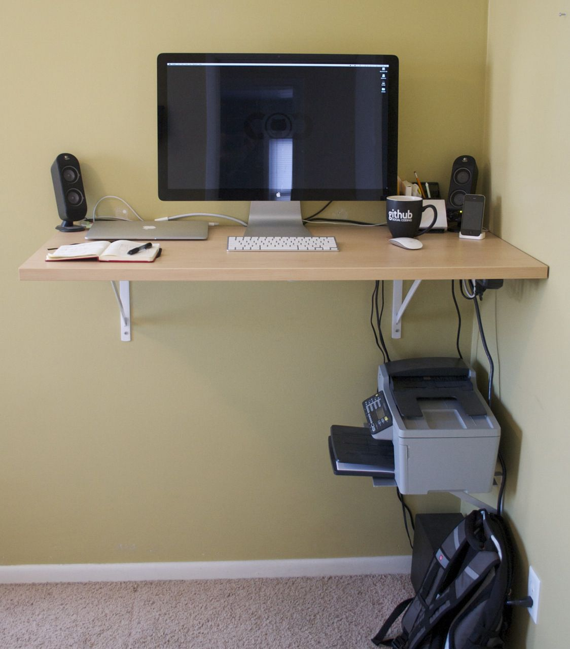 Small DIY wooden standing desk with a computer on top attached to a yellow wall.