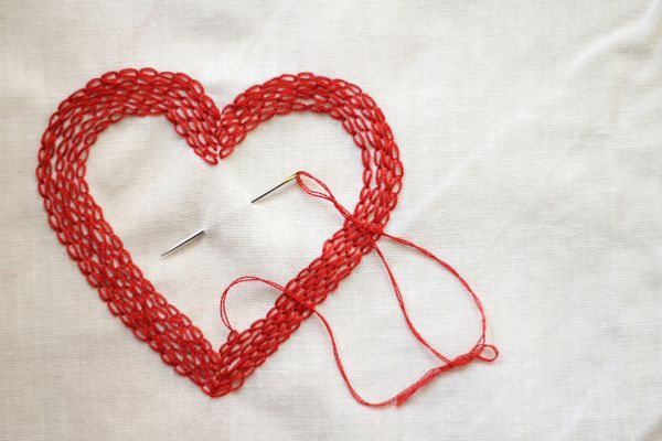 Red love heart made with needle and thread