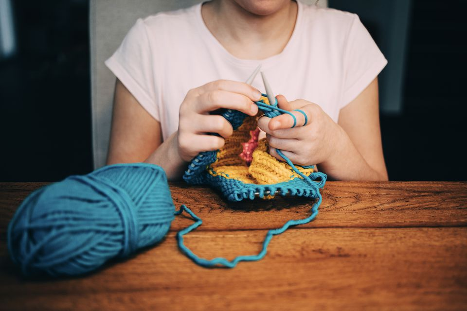 Girl knitting a hat in the round