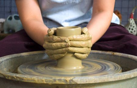 Close up of female potters hands making bowl