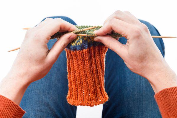 Woman knitting fair-isle sock