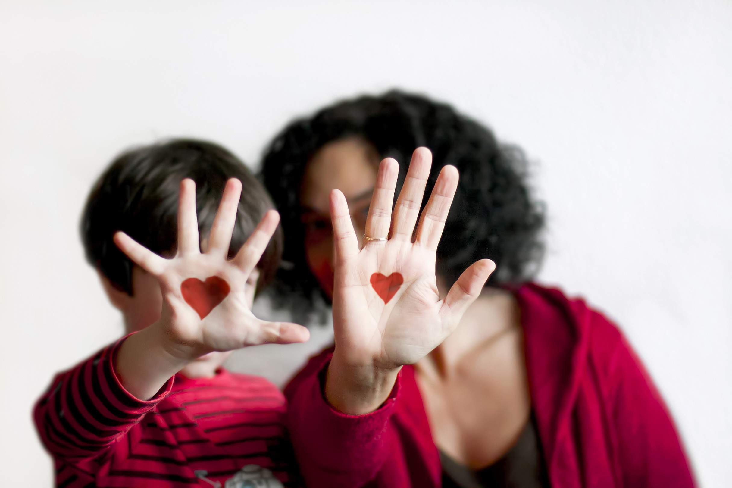 Mother and son with hearts painted on their hands