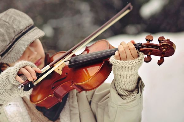 Woman wearing fingerless gloves while playing the violin.