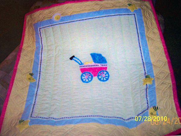 Baby carriage on a quilt.
