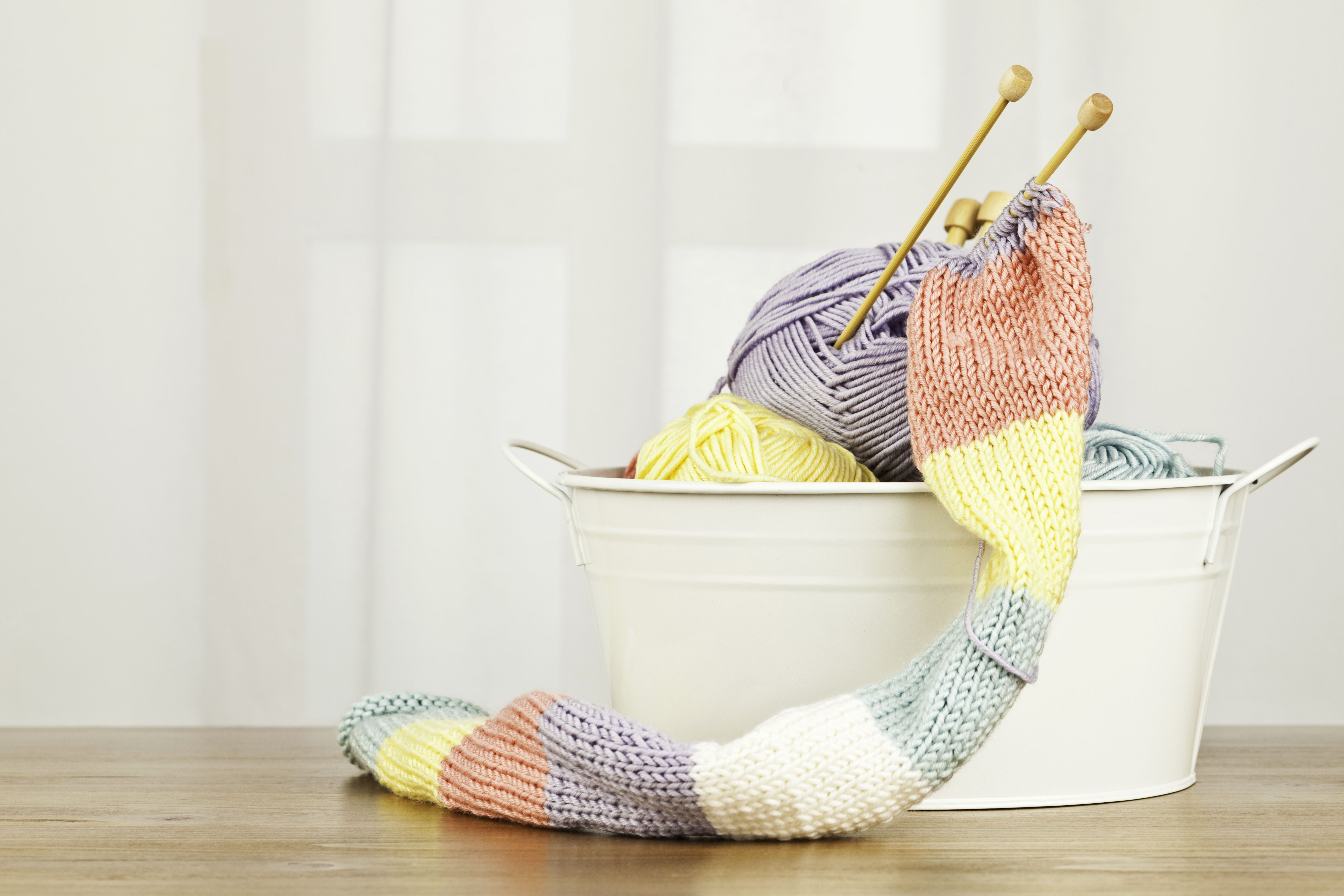 Hand-knitted scarf and yarn in a bucket.
