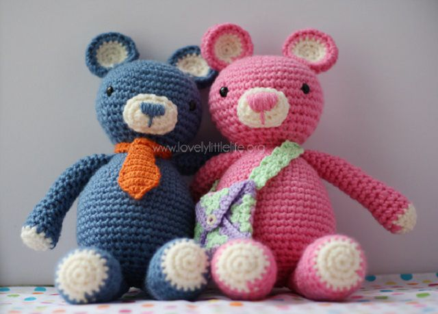 One blue and one pink crochet bear sitting next to each other.