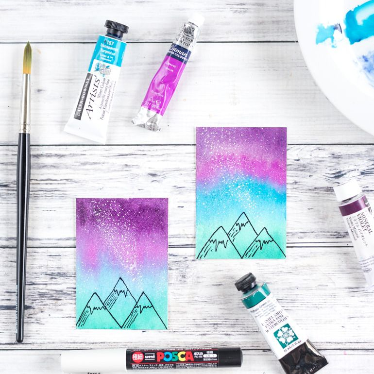 Two watercolor galaxy paintings on a white wood background