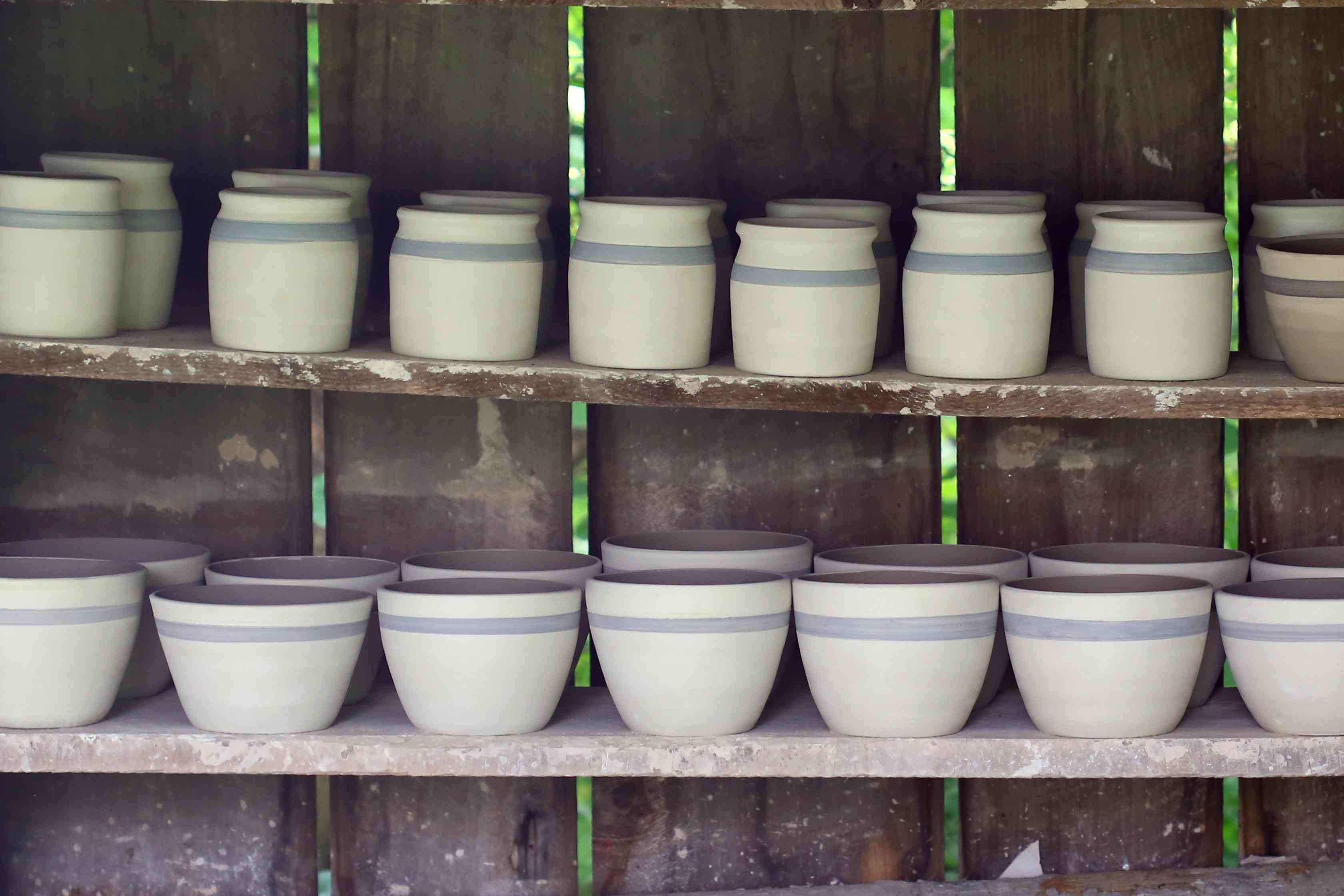 Rows of pottery aligned on simple utility shelves