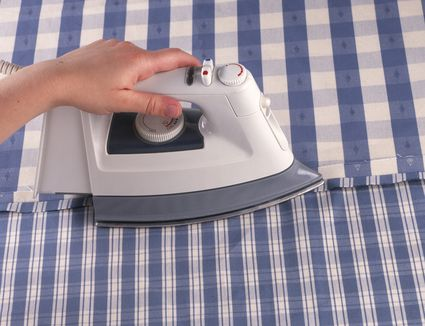 Person using an iron to pressing a seam open on a blue-and-white striped fabric.