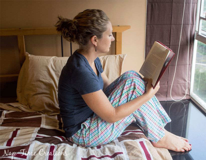 A woman sitting on her bed reading