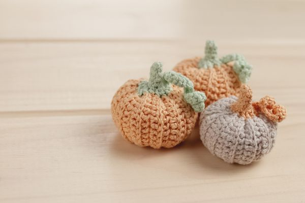 three crocheted handmade pumpkins on a wooden table, selective focus