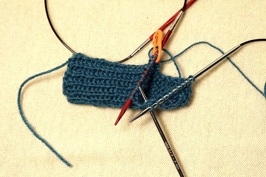 Forming the gusset of a blue crochet sock.