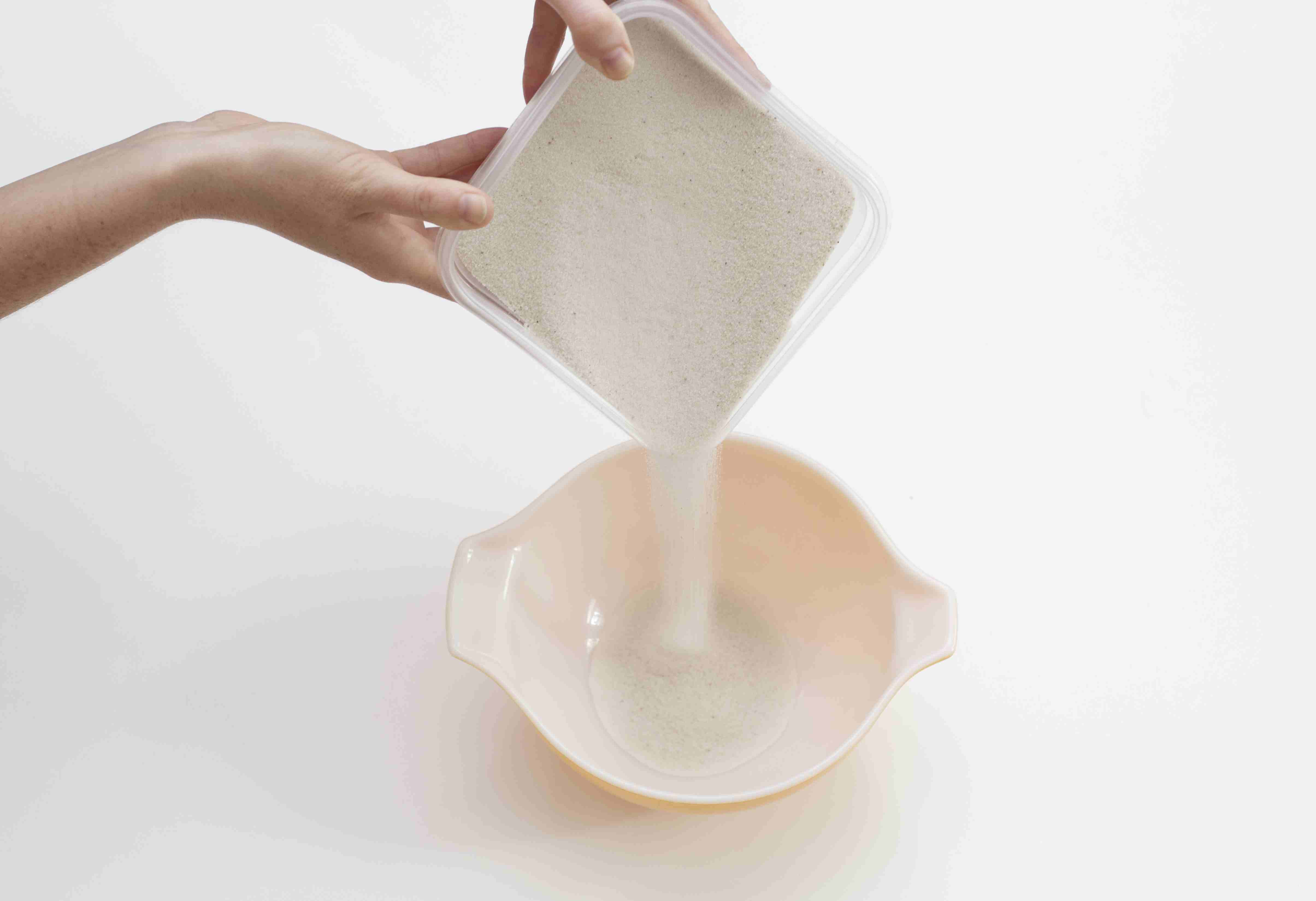 Pouring white sand into a bowl