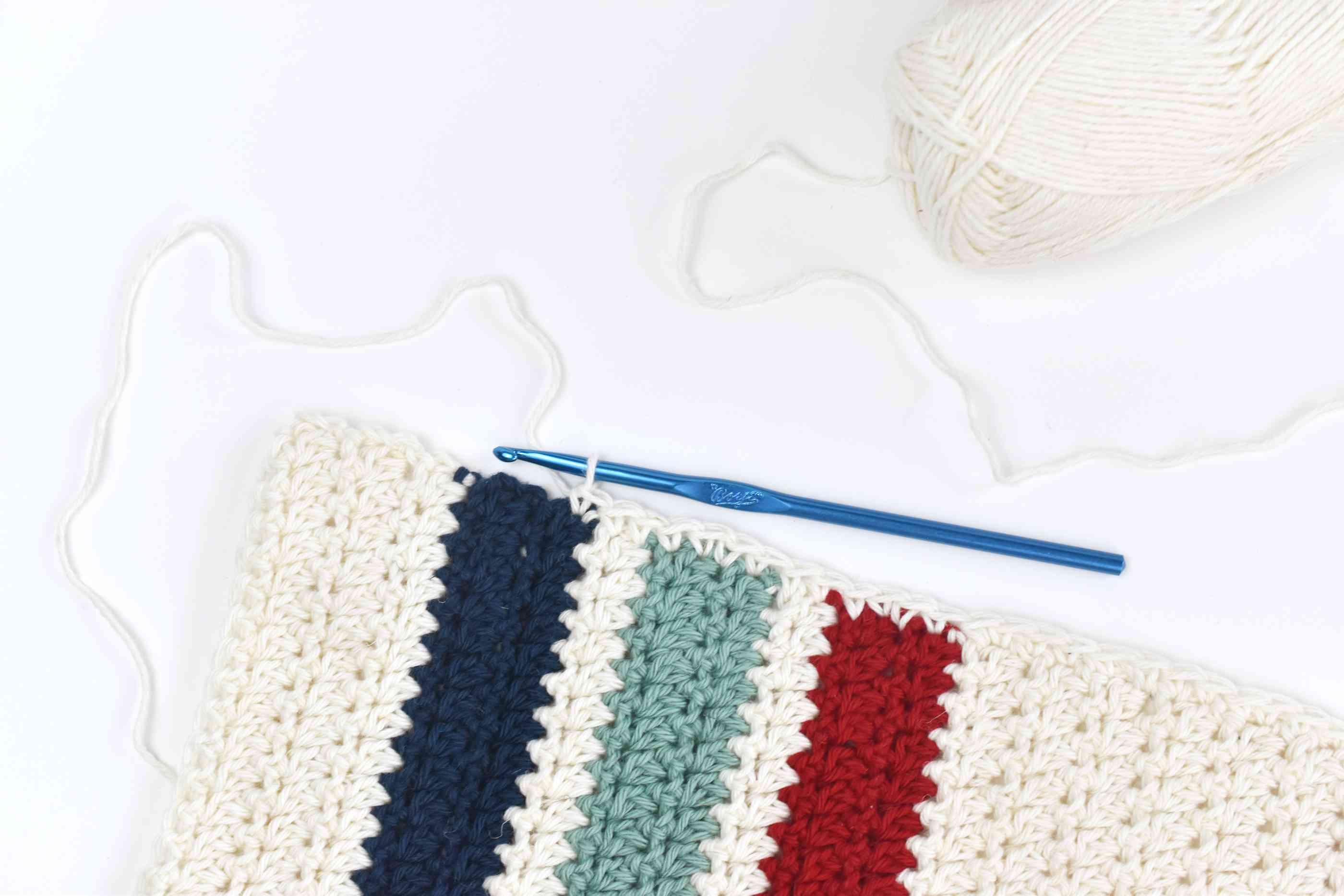 Blue crochet hook creating a border with white yarn along the dishtowel.